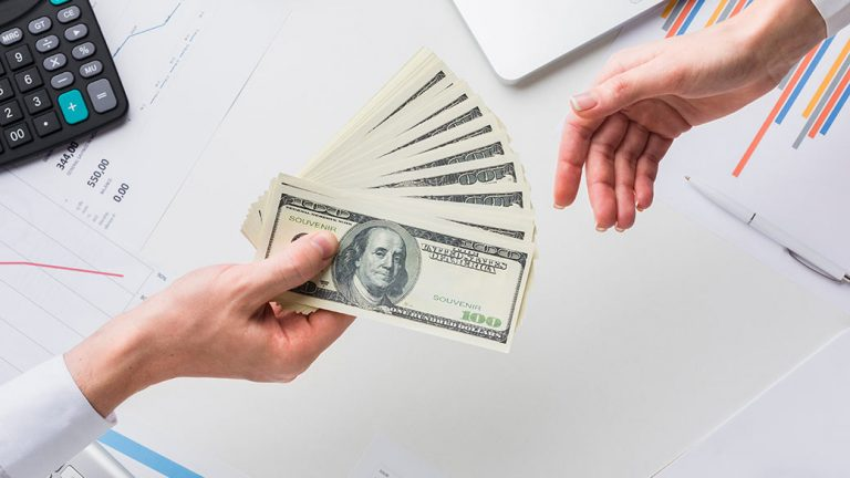 image: cash loan being handed to a business